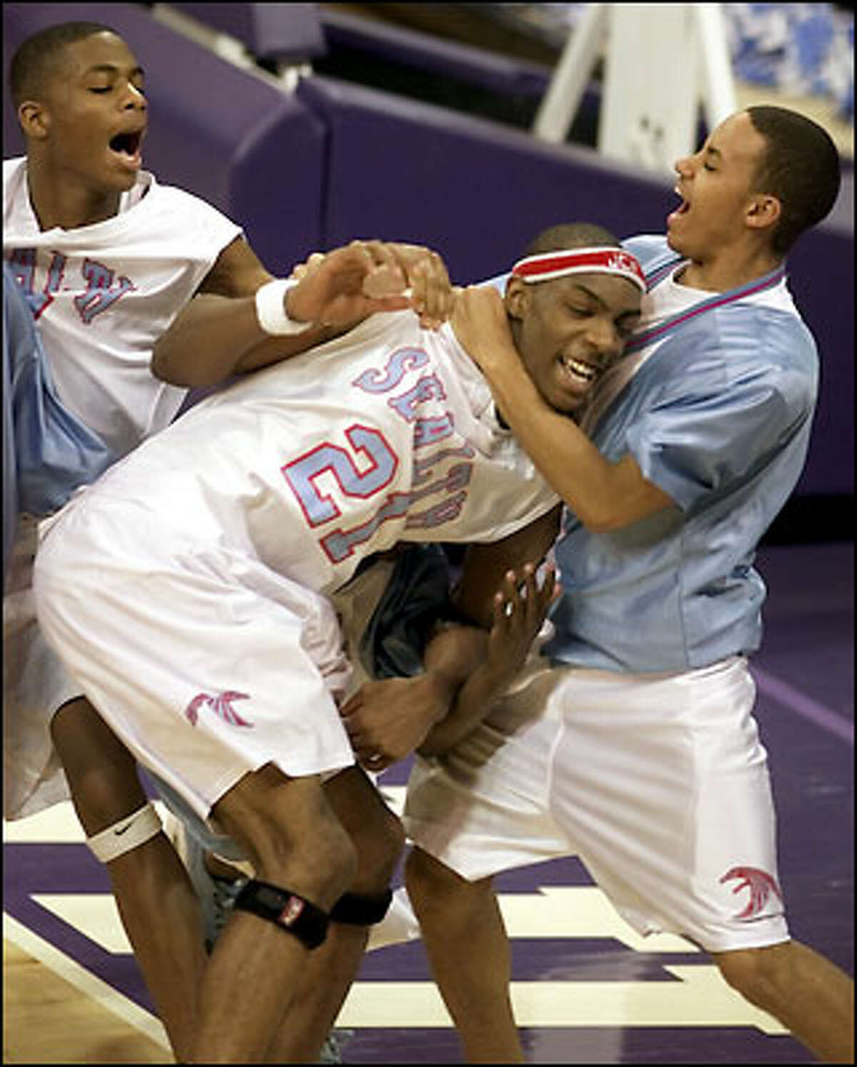 Chief Sealth's Erroll Knight is mobbed by teammates Devon Hall, left, and Joseph Hill after Knight made the game-winning basket at the buzzer in a 59-58 victory over defending state 3A champion Seattle Prep. Sealth will play Rainier Beach for the Sea-King district title.