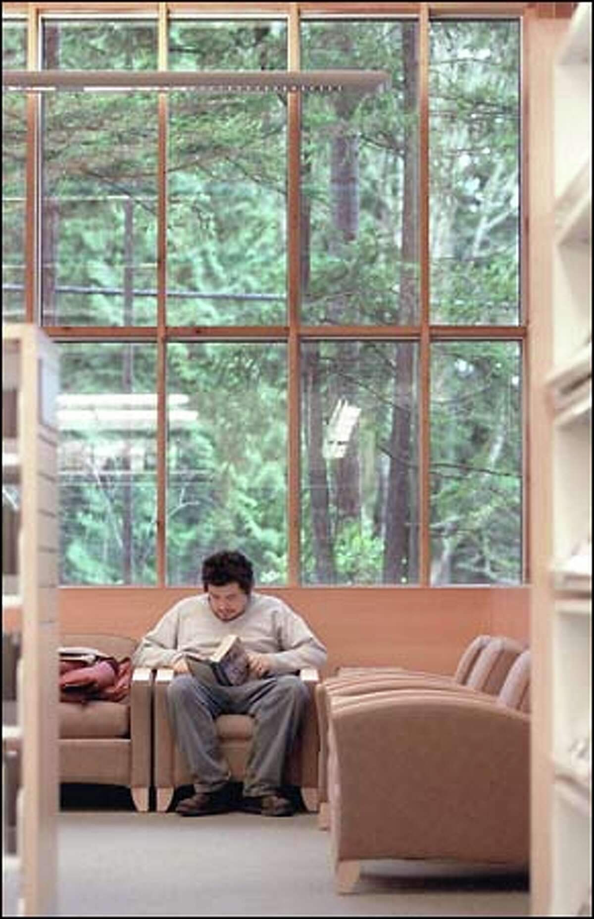 """Glenn Lewis finds a comfortable spot to read """"The Goebbles Diaries"""" at the Maple Valley Library."""