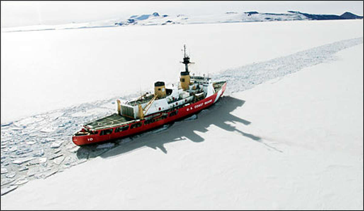 Polar Star cuts through ice on McMurdo Sound so that ships can resupply the U.S. station there. The brown hill, upper right, is Observation Hill at McMurdo. (1999)
