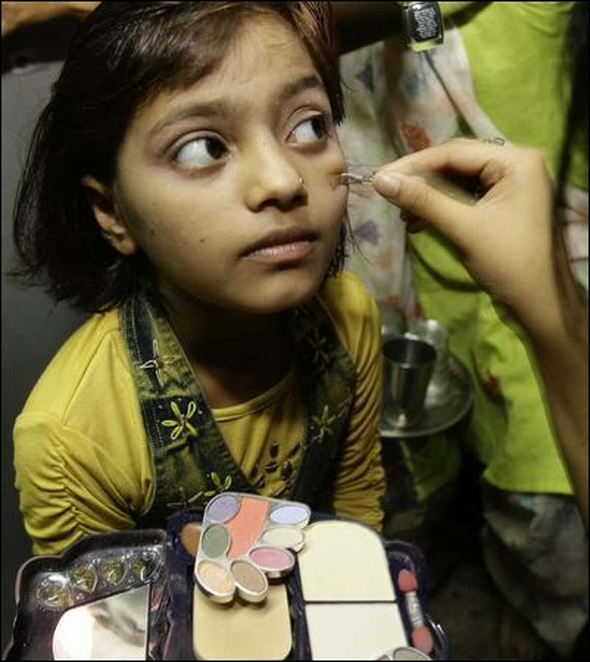 A relative applies makeup to Rubina Ali before she departs for L.A. and the Oscars.