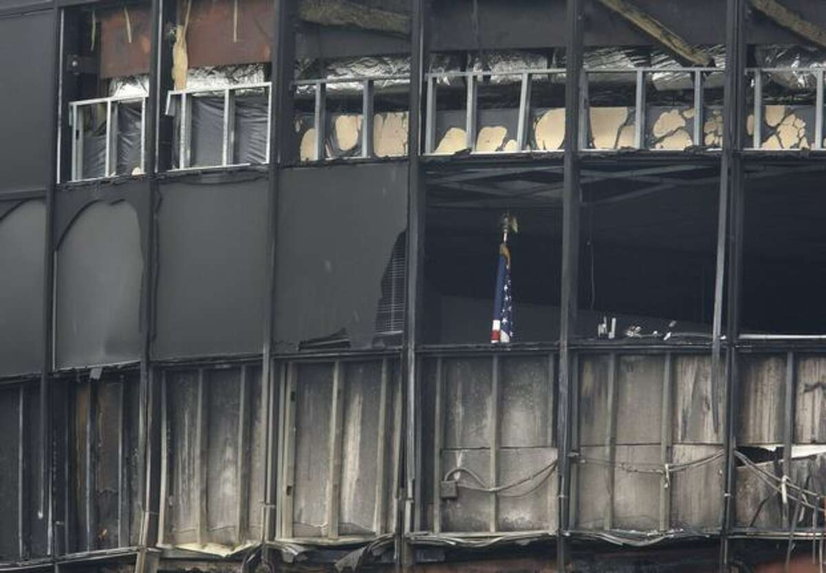 An American flag can be seen Saturday in Austin, Texas, through a broken window in a building that was destroyed when a small plane crashed into it Thursday. Authorities said that Joseph Stack flew his small airplane into the building shortly after taking off from Georgetown Municipal Airport. The building served as offices for several Internal Revenue Service employees. (AP Photo/Tony Gutierrez)