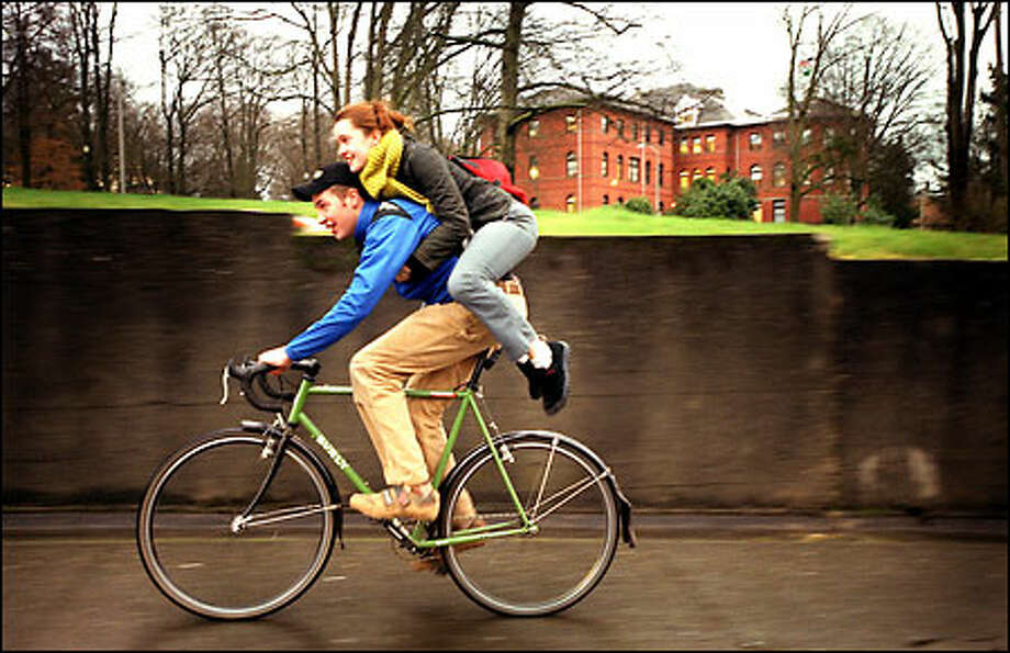 Adrian Hegywary, 18, carries some extra baggage – his friend Neysa Bell – up a hill on 15th Avenue Northeast near the University of Washington campus. Bell, 18, piggybacked home because it was quicker than walking and lessened the amount of time she had to be in the rain. Today's forecast calls for more lingering showers with a high of 51 degrees. Photo: Joshua Trujillo, Seattlepi.com / seattlepi.com
