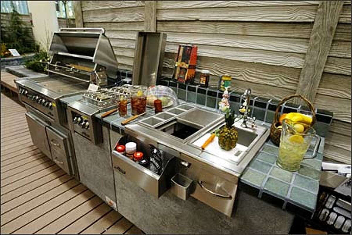 This outdoor kitchen features a grill with fridge below, gas cooktop and sink.