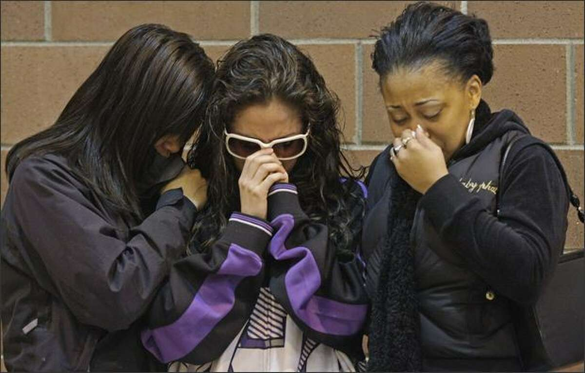 Young women comfort each other during a community rally held in response to the death of Tyrone Love, a Garfield High graduate, at the Garfield Community Center in Seattle on Saturday. Twenty-six-year-old Love, a popular party promoter, was gunned down in the Central District on Monday.