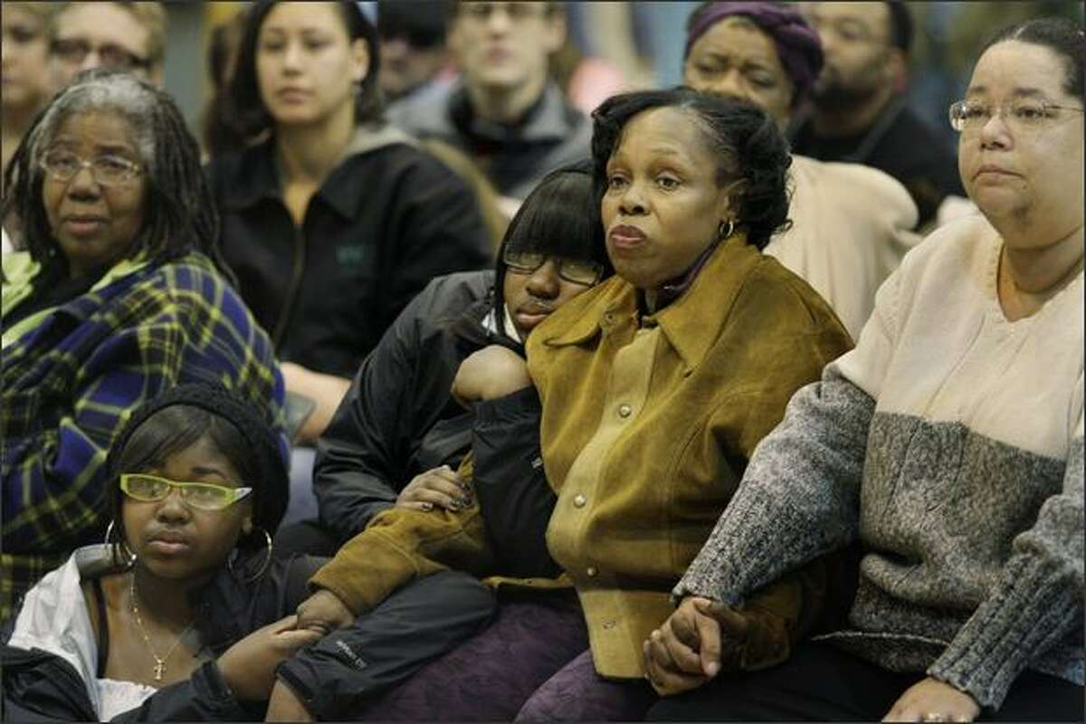 Roberta Love-Harrison (second from right) is comforted by her daughter Christyna Bradford during a community rally held in response to the death of Harrison's son Tyrone Love. With them are (from left) Rev. Harriett Walden, Thessemay Webber and Joyce Williams, family friends.