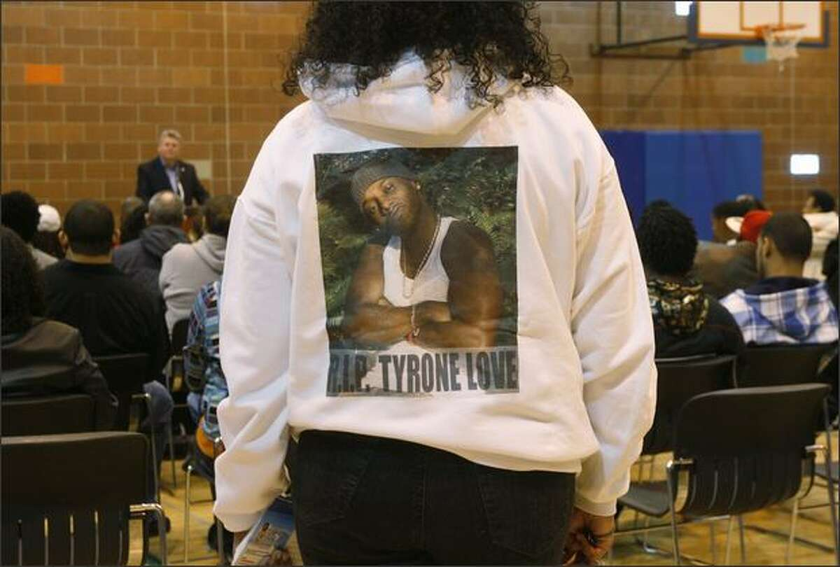 A woman, wearing a sweatshirt bearing an image of Tyrone Love, listens to Seattle Mayor Greg Nickels during a community rally held in response to the death of Love.