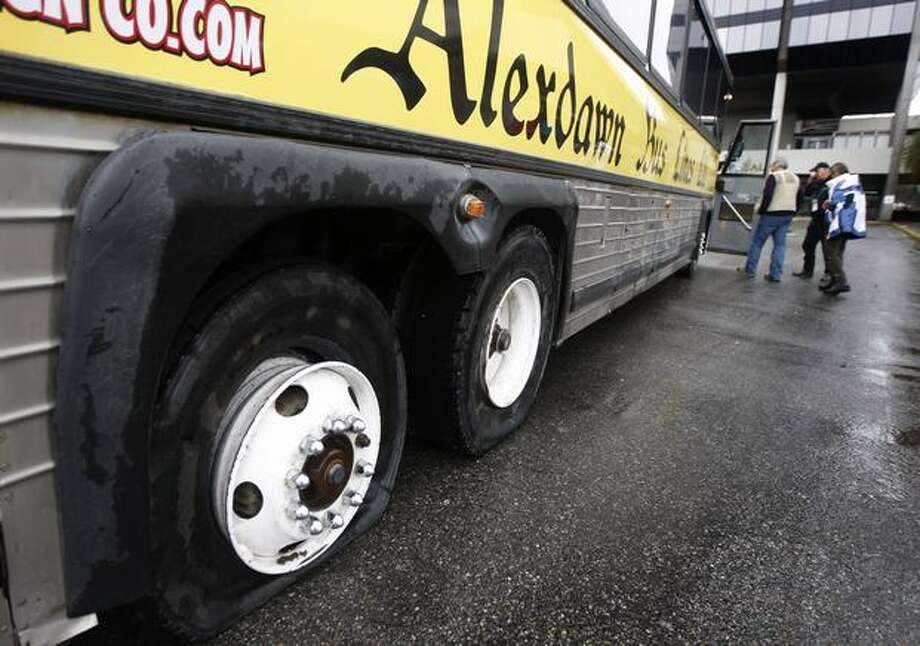 A bus transporting journalists to Cypress Mountain to cover a moguls event at the Winter Olympic Games received two flat tires after the driver got lost and struck a sign post while detouring through a small shopping center in West Vancouver, B.C. Photo: Paul Chinn, Hearst Newspapers / Hearst Newspapers