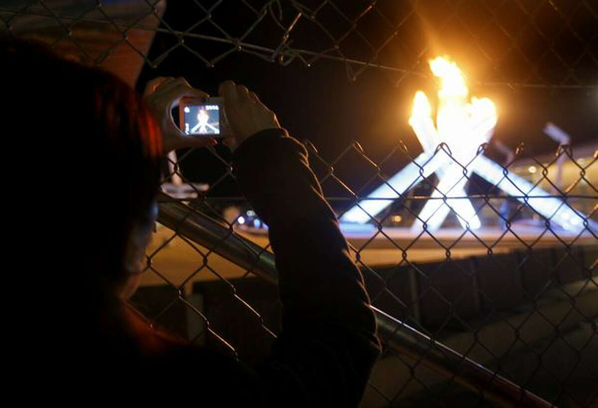 A woman snaps a photo of the Olympic cauldron through a slit in a fence surrounding the outdoor cauldron in Vancouver, B.C., on Friday, Feb. 19, 2010. Under mounting pressure, Winter Games officials improved access to the flame -- including replacing part of the fencing with a more camera-friendly plexiglass barrier.