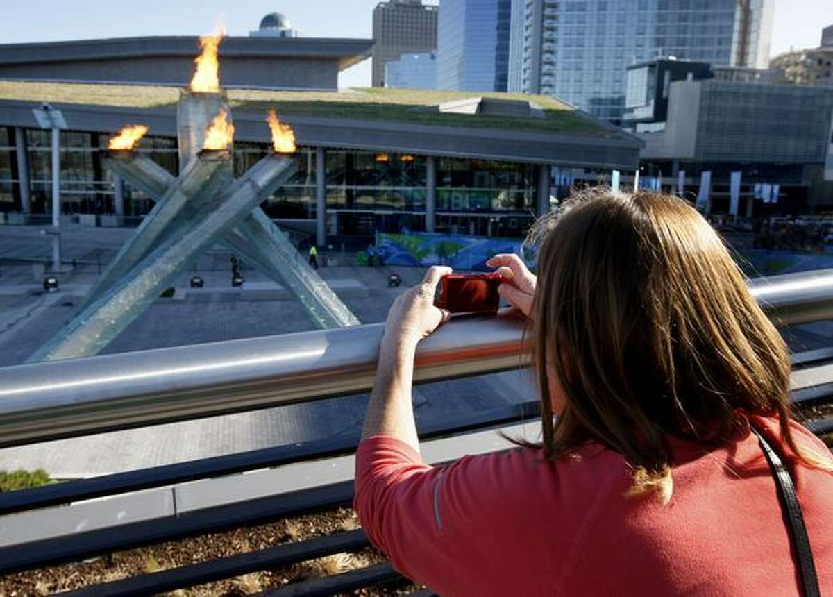 Ann Madsen of Lynnwood, Wash., takes a photo of the Olympic cauldron from an elevated overlook in Vancouver, B.C., on Saturday, Feb. 20, 2010. Under mounting pressure, Winter Games officials improved access to the flame.