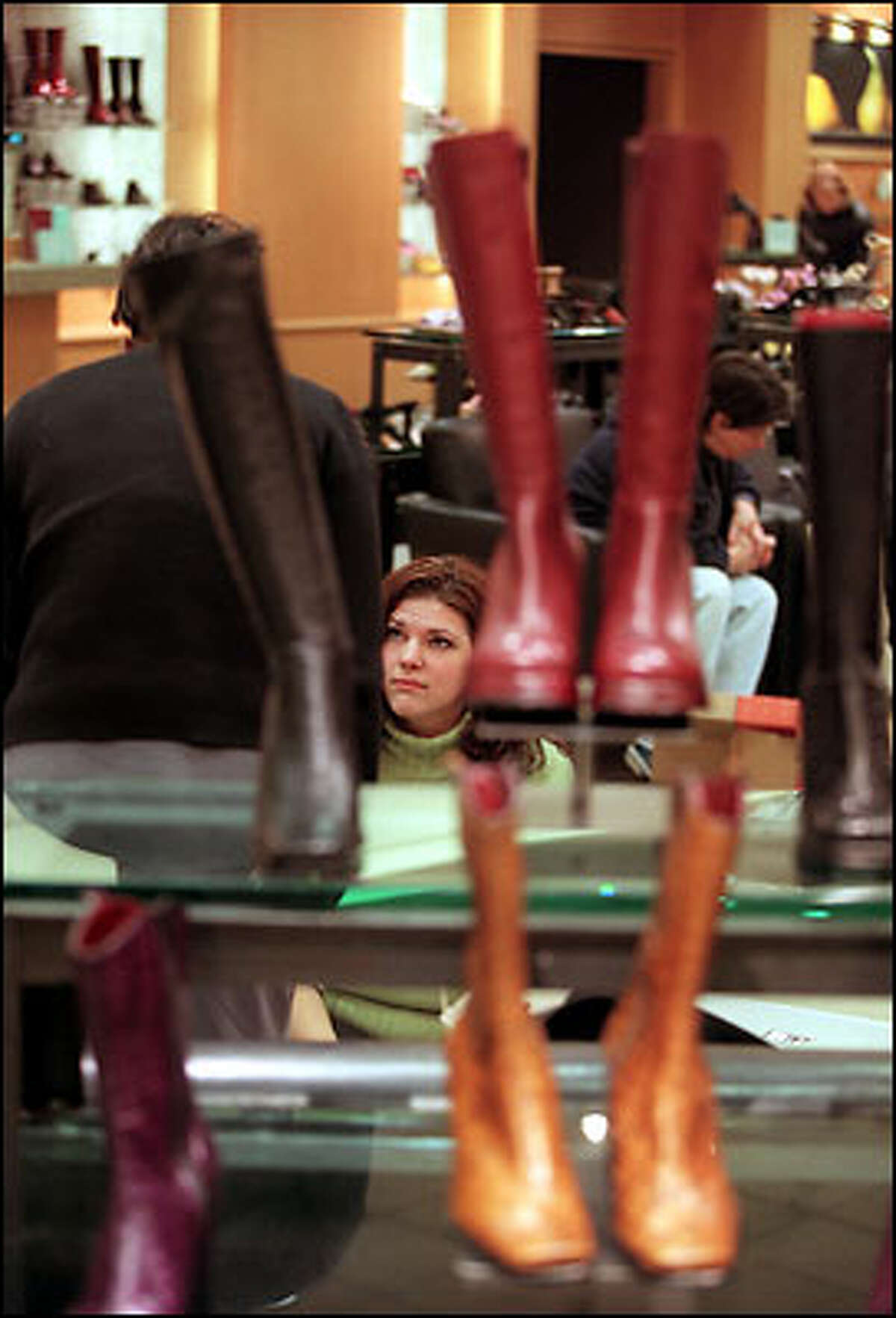 Saleswoman Nicole Wierzbicki, center, fits Fabiola Phillipi with a new pair of boots in the downtown Seattle store.
