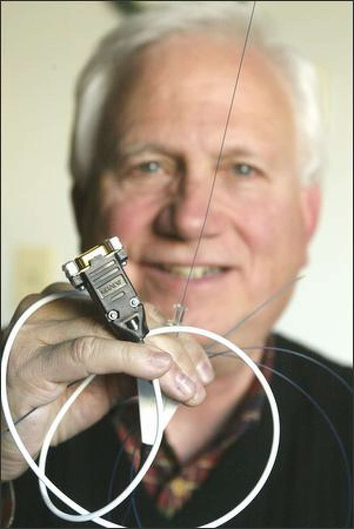 Ekos co-founder Douglas Hansmann holds an ultrasound catheter that helps doctors quickly dissolve blood clots. As part of its ramp-up, the company plans to double its 50-person staff in the next 18 months.