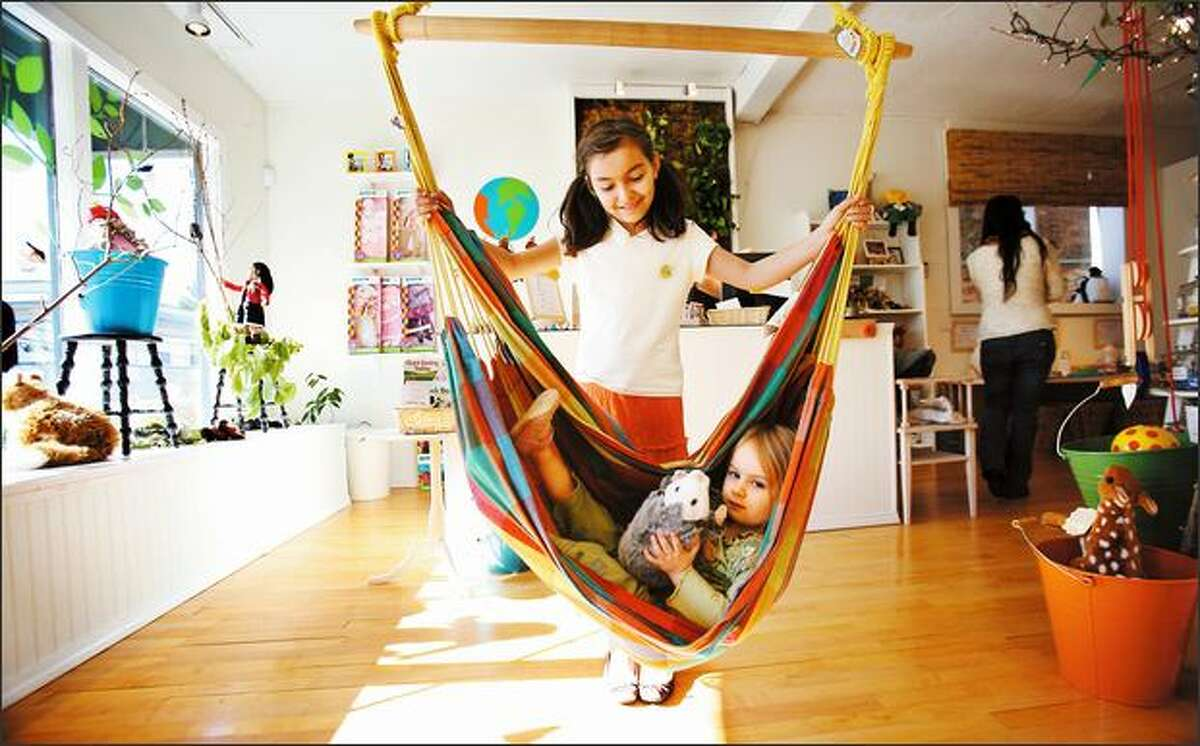 Isabella Faget, 3, tries out the hammock at Planet Happy Kids in Ravenna on Friday with the help of Hannah Kohrmann, 10. The showroom for the larger online company sells fair-trade, organic, socially responsible, natural and green products for children.