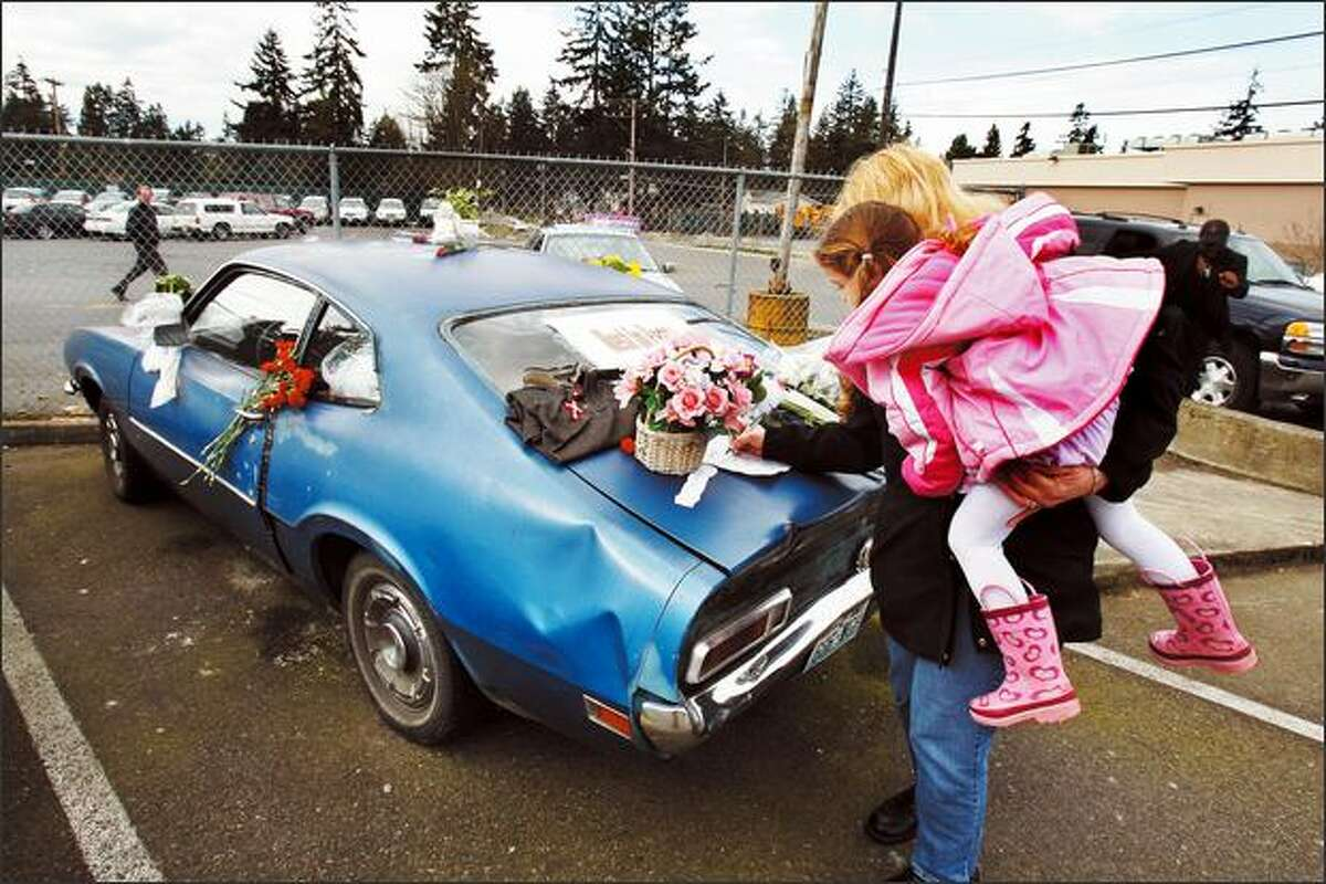 Edmonds resident Nancy Hanthorn, with 3-year-old daughter Kristina in tow, signs a