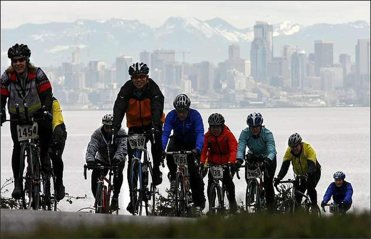 With the Seattle skyline behind them, riders head toward the finish of the Chilly Hilly bicycle ride on Bainbridge Island on Sunday.