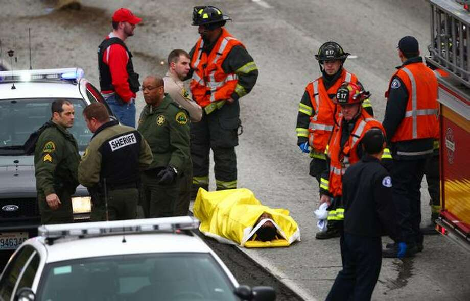 An injured man is surrounded by officers after a high-speed chase ended with a crash on Interstate 5 at NE 70th Street on Wednesday. Photo: Joshua Trujillo, Seattlepi.com / seattlepi.com