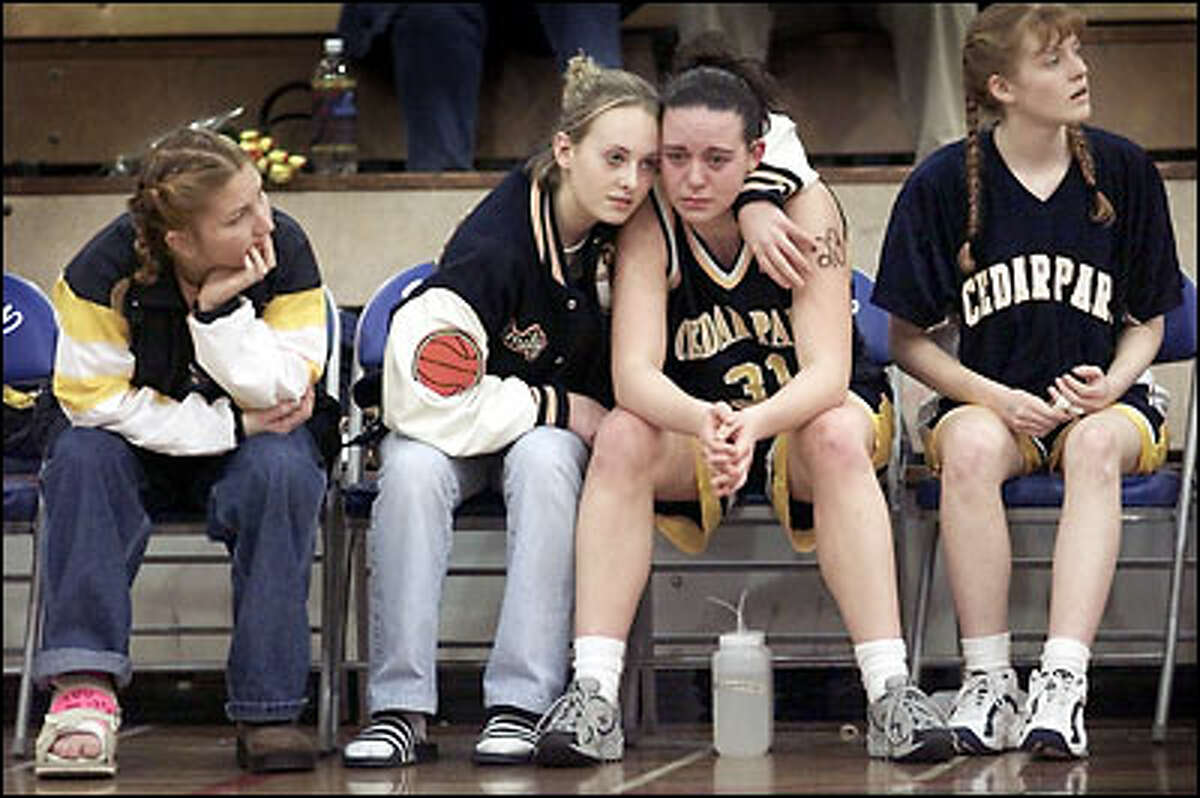 Cedar Park Christian High School's Emily Harrison comforts her tearful teammate, Mandy Janes, last night as their chance to advance in the girls Class B state tournament is ended by Shoreline Christian High School. Injured senior Julie Kirkland, left, and player Stacie Swicord, right, watch the game in Seattle's Ingraham High School gymnasium.