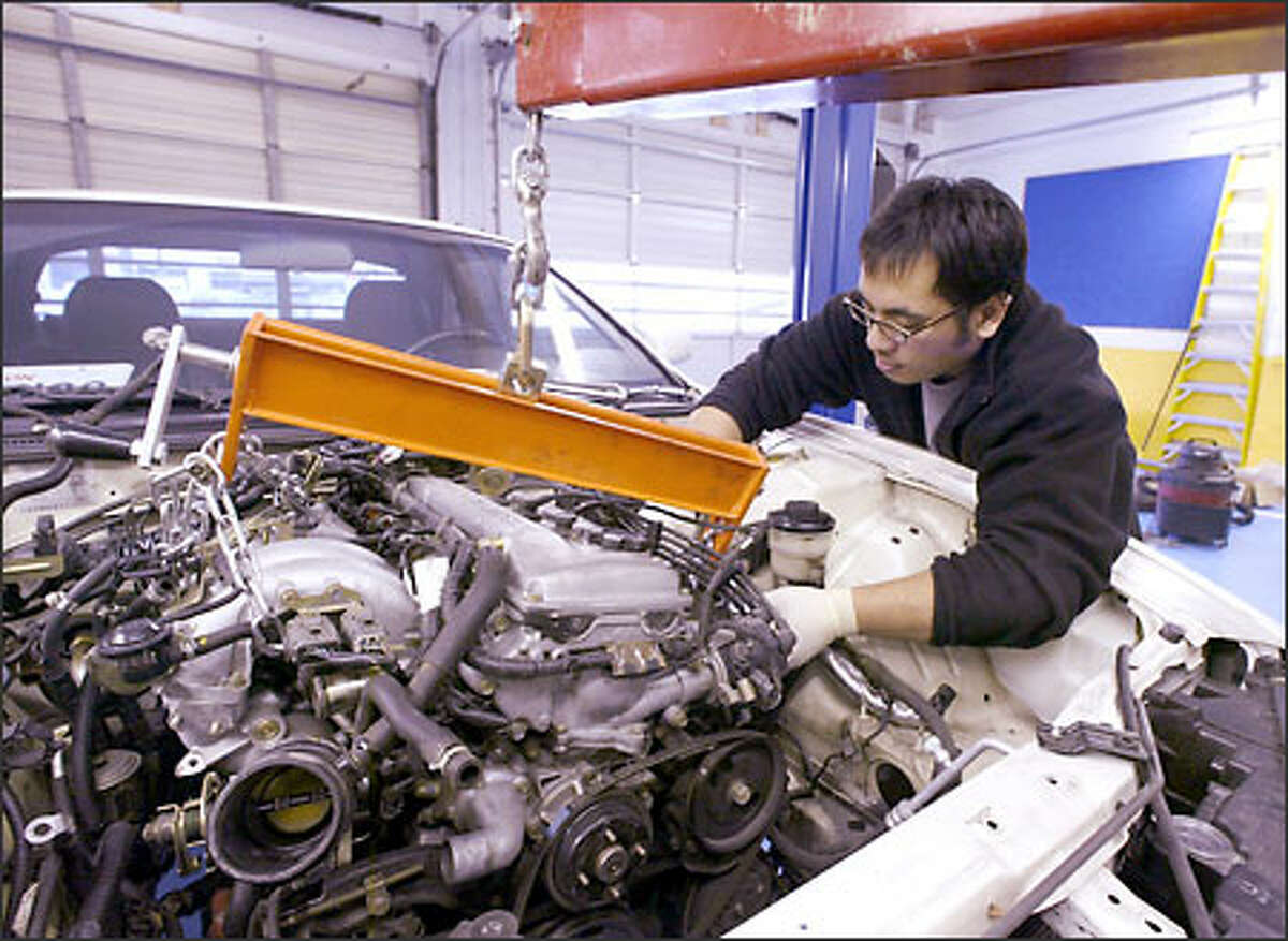 Christian Palacay works on a 1995 Nissan 240 at Speed Performance Garage. Importmix.com caters to young Asian Americans who enjoy the car show scene.