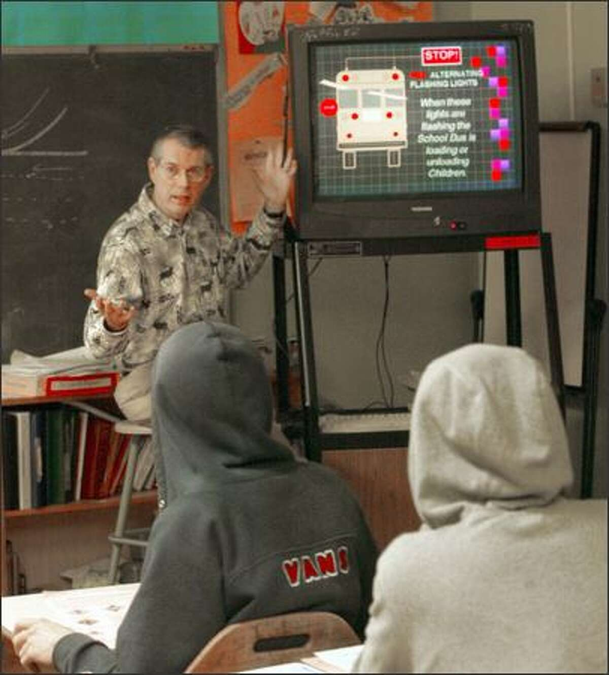 Larry Temple instructs students at Nathan Hale High School on the meaning of red lights on a school bus. As fewer students sign up for the public-school courses, the cost per student rises, and more schools drop the course.