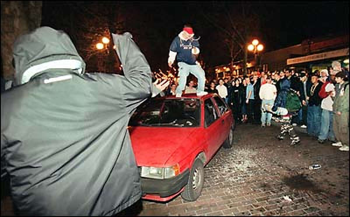 While a large crowd watches, a man jumps on top of a parked car that was seriously damaged when Mardi Gras celebrations in Pioneer Square degenerated into a riot early this morning.