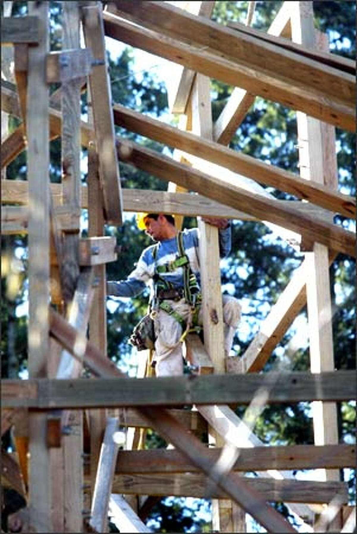 A worker helps put up the TimberHawk roller coaster at Wild Waves/Enchanted Village in Federal Way.