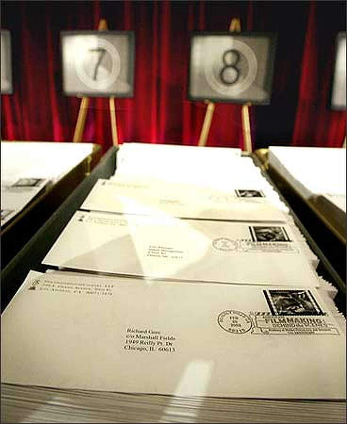 Trays full of final ballots for the 75th Academy Awards, with one addressed to actor Richard Gere strategically placed on top, are displayed on a stage at the Academy of Motion Picture Arts and Sciences in Beverly Hills, Calif., prior to being loaded aboard a mail truck Tuesday, Feb. 25, 2003. The envelopes carry commemorative postage stamps of the U.S. Postal Service's