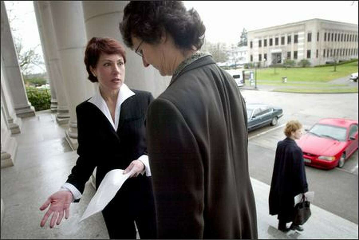 Gambling-treatment activist Jennifer McCausland, left, talks with state Rep. Eileen Cody before a meeting with Gov. Gary Locke last month in Olympia. McCausland says that her son died in a car accident because his gambling addiction left him with no money to properly maintain his vehicle.