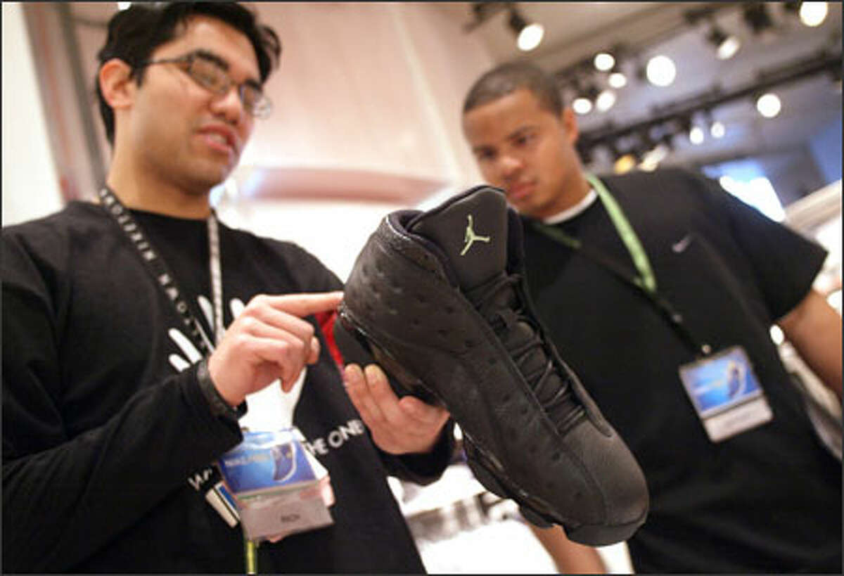 Sales clerks Rich Reyes, left, and Dominique Pie check out one of the Air Jordan Retro 13 shoes at Seattle's Niketown, which will sell only 60 pairs.