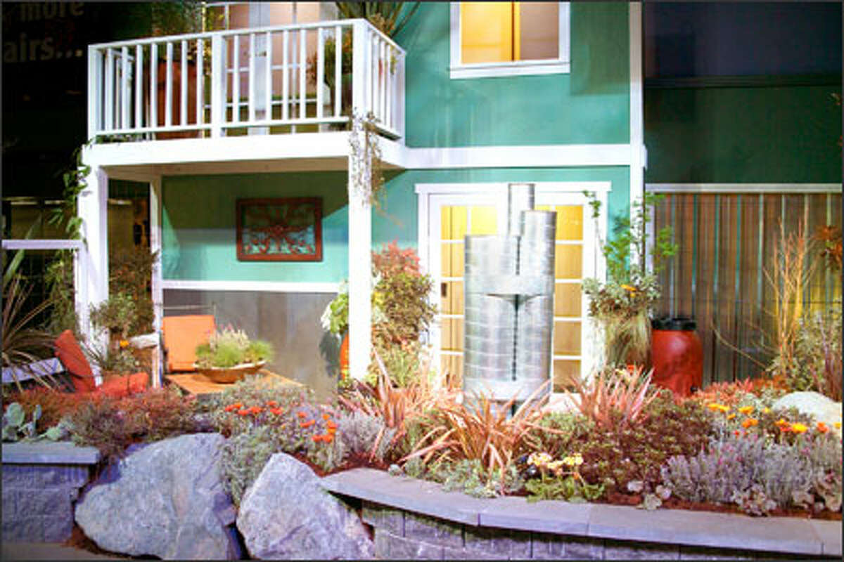 """Tami Ott-Ostberg's """"Small Space Style"""" display at the Northwest Flower & Garden Show demonstrated how gardeners could sit out on a patio near shiny metal air vents and still enjoy the scene. She incorporated the unmovable items into the display by turning them into a water feature."""