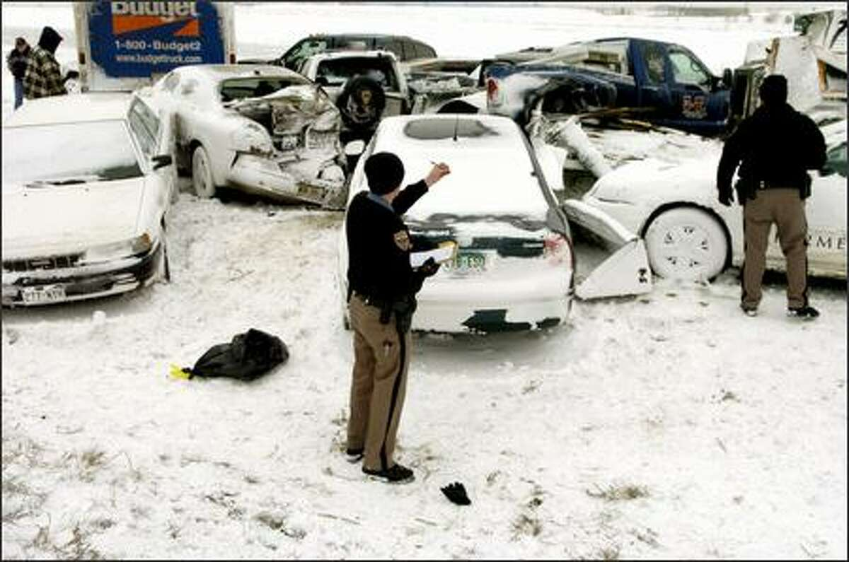 Aaron Limburg, of the Colorado State Patrol, takes notes at the scene where more than two dozen cars collided in whiteout conditions on Interstate 70 early Saturday in Aurora, Colo. Blowing snow reduced visibility to almost nothing when the accident happened. No major injuries have been reported in the pileup.
