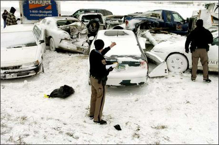 Aaron Limburg, of the Colorado State Patrol, takes notes at the scene where more than two dozen cars collided in whiteout conditions on Interstate 70 early Saturday in Aurora, Colo. Blowing snow reduced visibility to almost nothing when the accident happened. No major injuries have been reported in the pileup. Photo: Associated Press / Associated Press