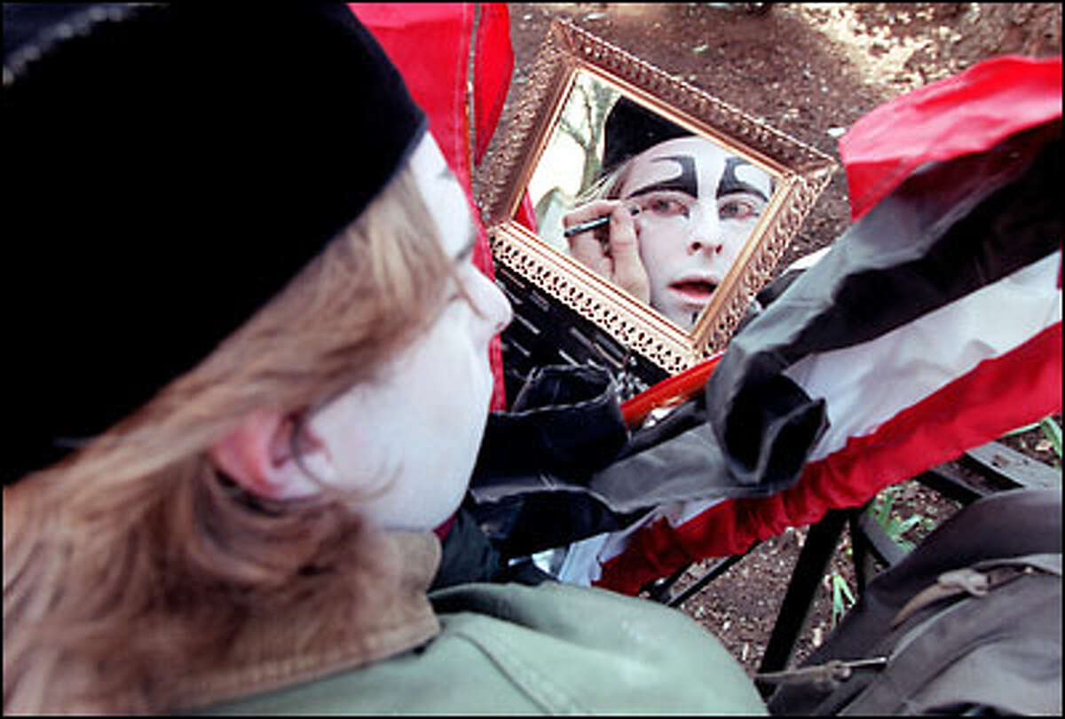 John Murphy, 31, from the performance group Cabiri in Seattle, applies makeup before mounting his stilts at the Mardi Gras parade yesterday at Pioneer Square in Seattle. He won best overall costume for his get-up, which, at 16 feet, made him the tallest at the festival.