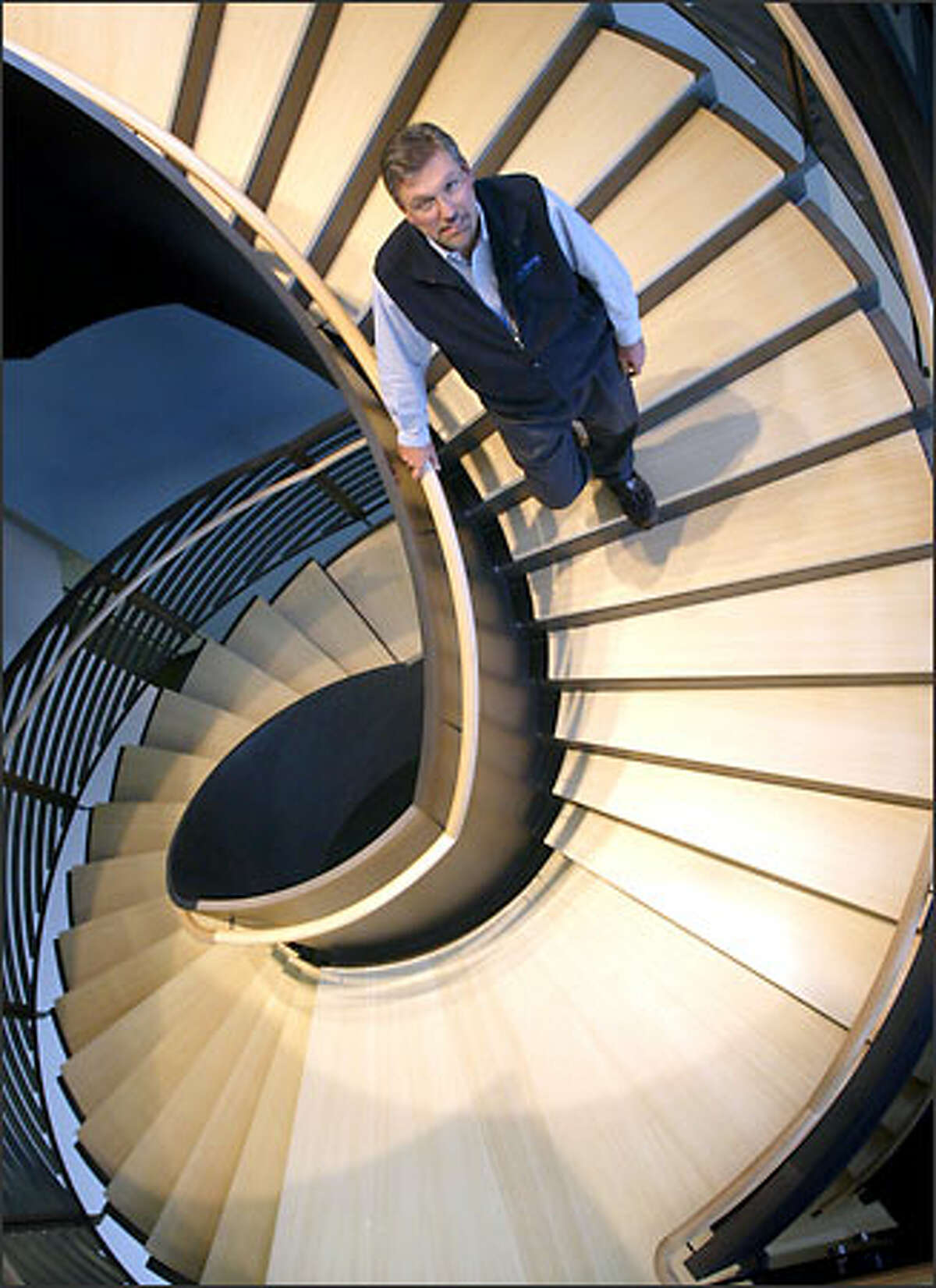 Randy Hassler, vice president of operations and quality for Amgen, shows off one of two spiral staircases inside the new campus.