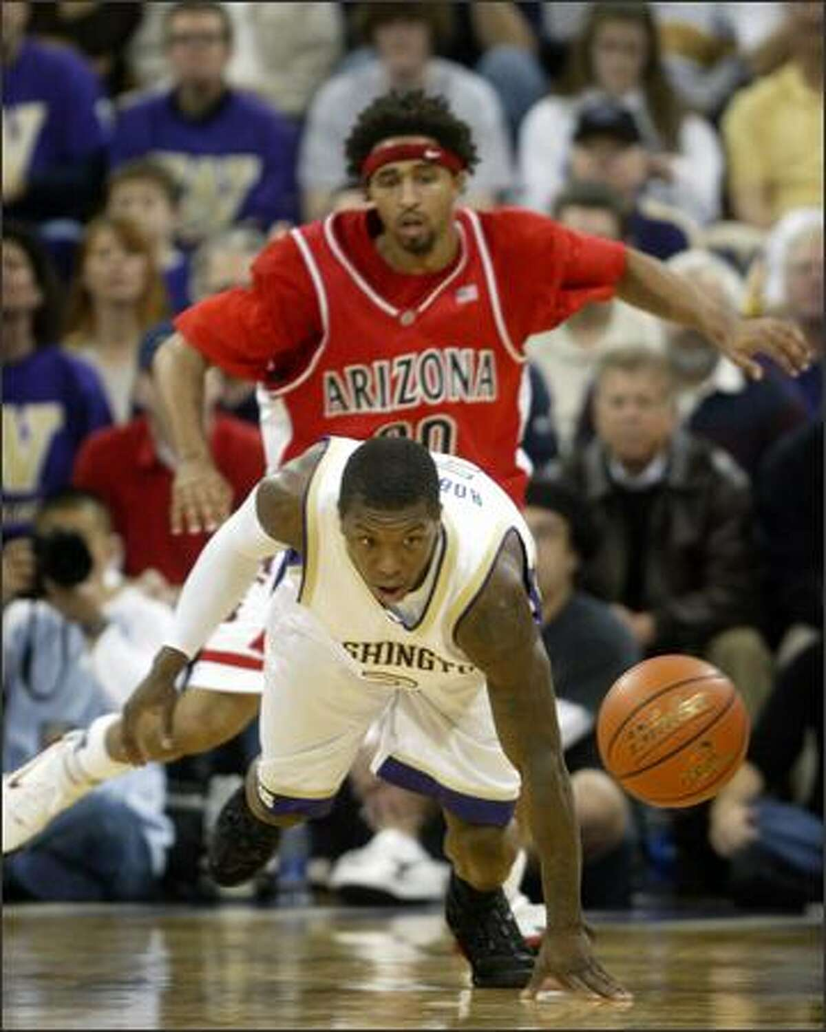 University of Washington player Nate Robinson scrambles for a loose ball with University of Arizona player Salim Stoudamire on Saturday.