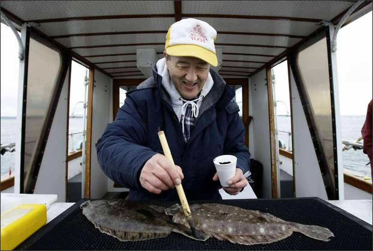 Masaro Tahara, former president of the Tengu Club, paints a flounder with ink Sunday before putting paper over it to make a print while fishing near Hansville.