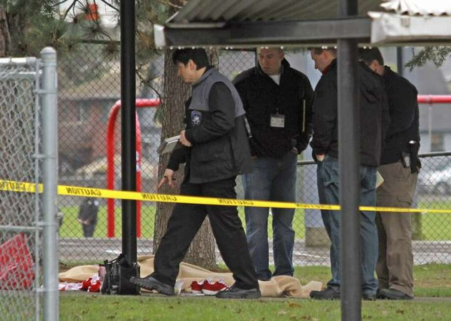 Tacoma Police officers investigate the slaying of special education teacher at Birney Elementary School in Tacoma. The suspect in the shooting was fatally shot by Pierce County sheriff's deputies shortly after. (AP Photo/The News Tribune, Dean J. Koepfler) Photo: Associated Press / Associated Press