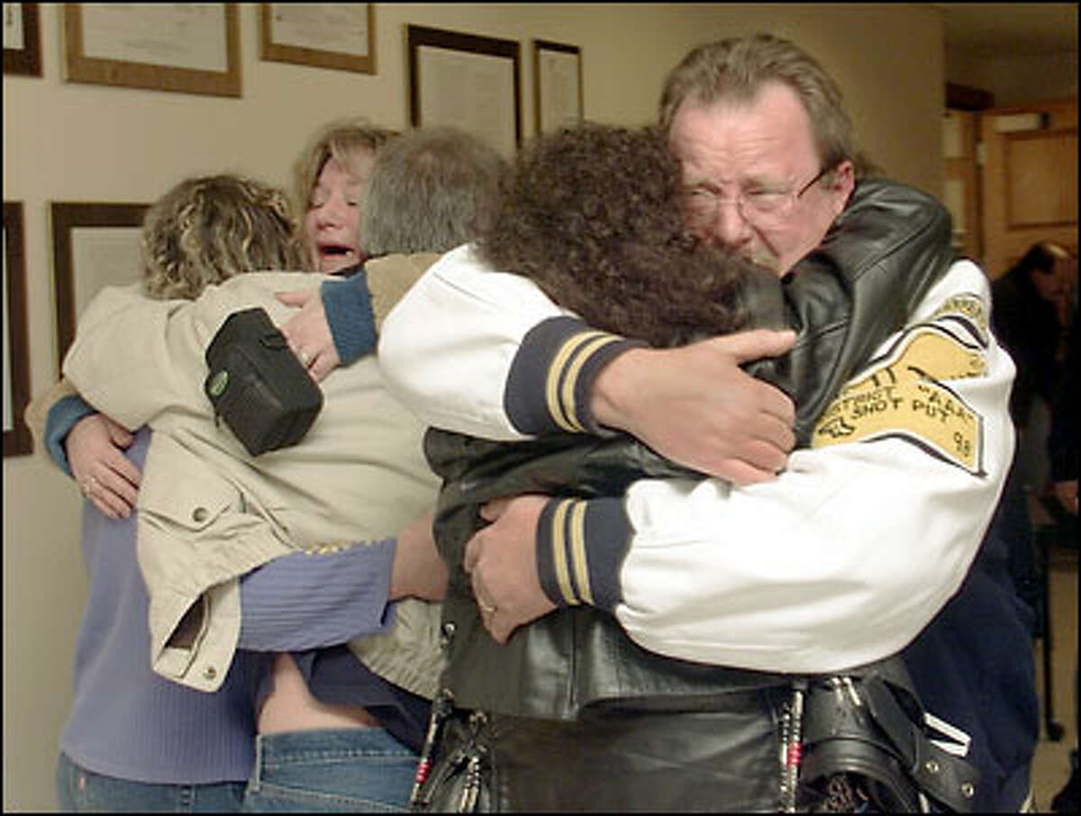 Sonny Thompson, father of Jason Thompson, who was slain by Dennis Cramm, hugs an unidentified person after a first-degree guilty verdict came in yesterday in Everett.