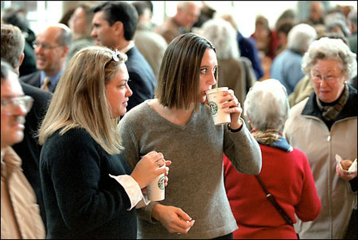 Joey Watters, left, and Janet Gray, Starbucks shareholders, have a cup of coffee before going to the annual shareholders meeting at Benaroya Hall yesterday.