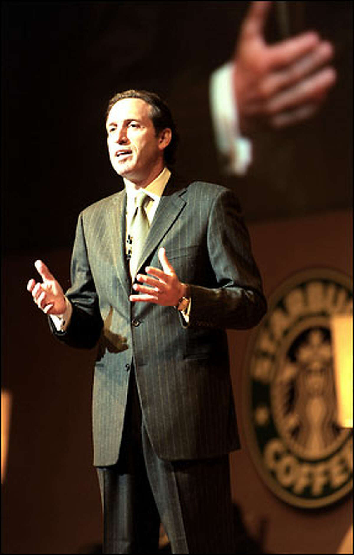 Howard Schultz, Starbucks chairman and chief global strategist, talks to shareholders yesterday during their annual meeting in Seattle.