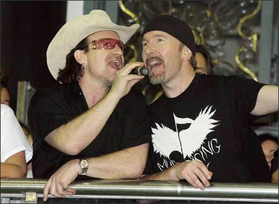 "Bono and the Edge perform during Carnival in Salvador, Brazil. What do you think the chances are that they're doing a cover of Kevin Federline's ""PopoZao?"" Given that they're not being pelted with rocks, we'll assume they're singing something good while attending as guests of the culture minister and pop star Gilberto Gil. Photo: Associated Press / Associated Press"