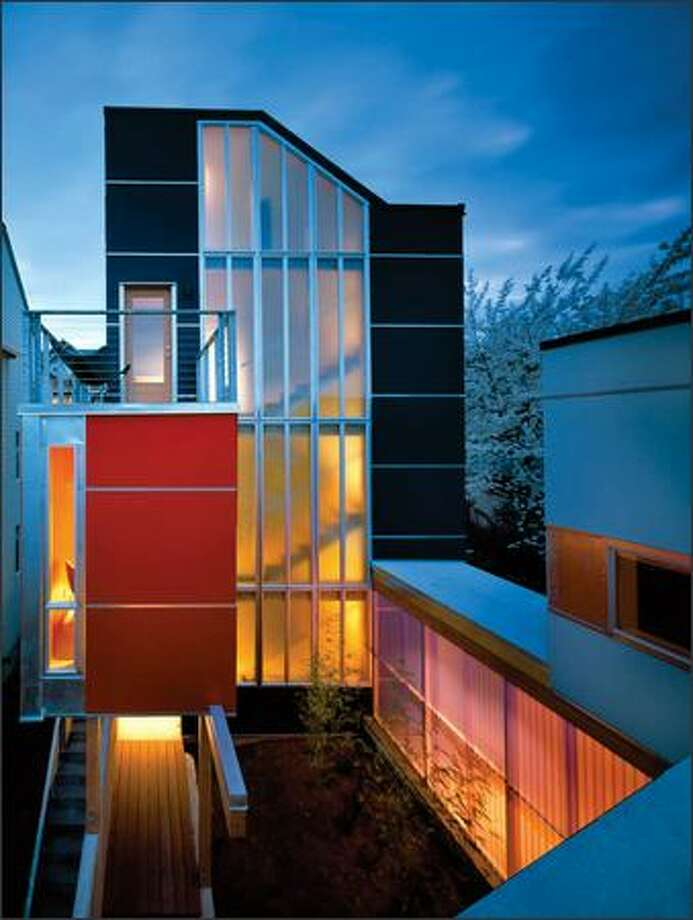 "The perky, colorful stair tower of the ""Envelope House's"" back dwelling rises above the compact courtyard between the two units. The corridor at lower right connects the two."