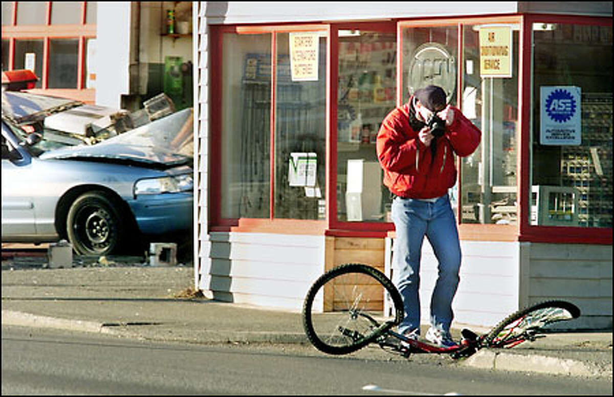 Seattle Police Detective Randy Huserik photographs the bicycle of a man who was fatally injured in a crash with a police cruiser, shown in the background, early yesterday.