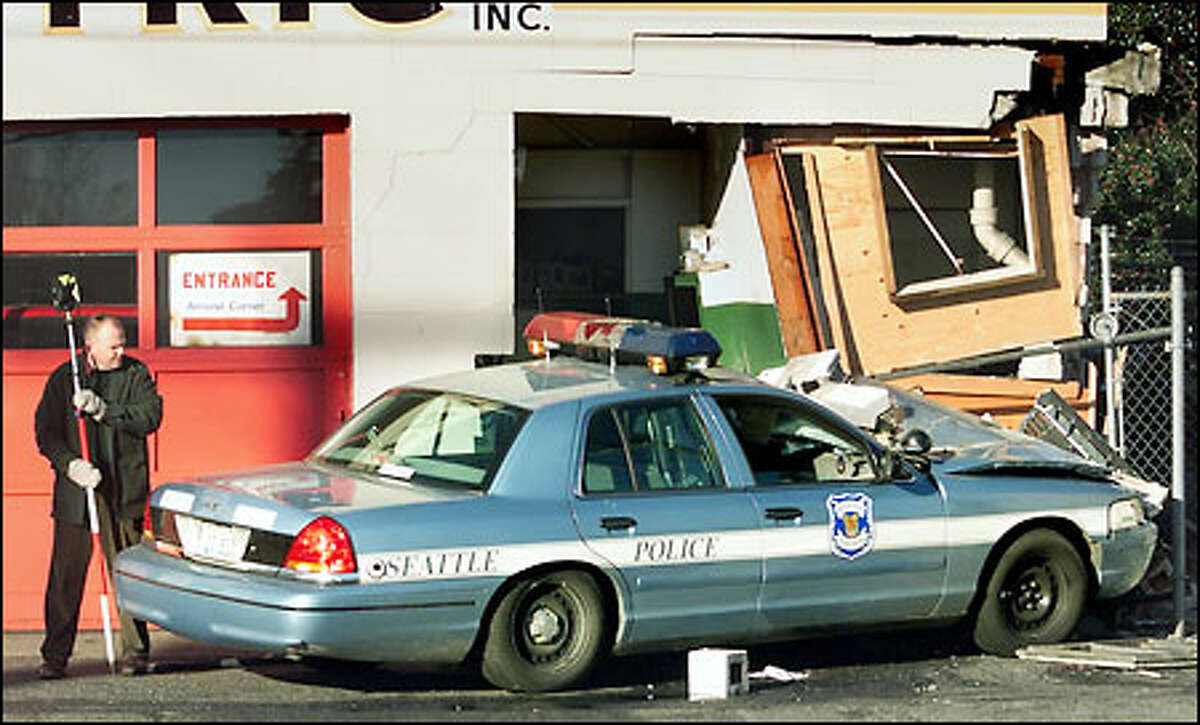 The police car crossed the southbound lanes of Aurora Avenue North and demolished a corner of a building before coming to rest.