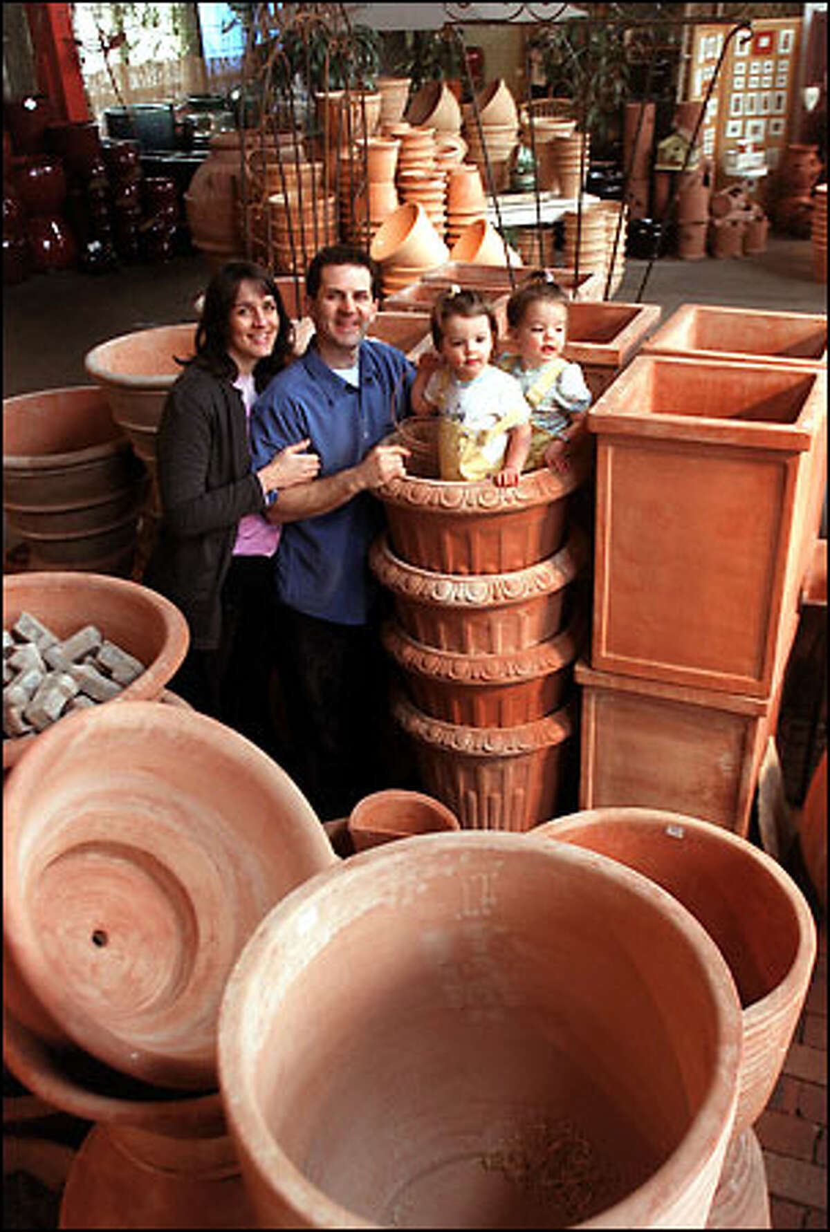 Alison Bockus and her husband, Dan, shown with twin 2-year-old daughters Maisy and Madison in their Herban Pottery store at 3220 First Ave. S., are
