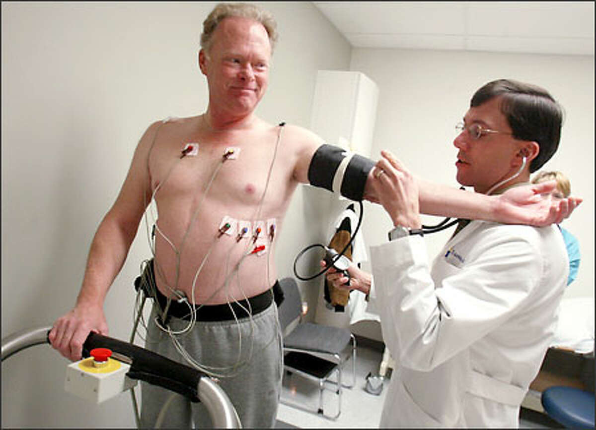 Dr. Tom Amidon checks Ken Schwarz's blood pressure. Schwarz is part of an experiment using gene therapy to regrow blood vessels in the heart.