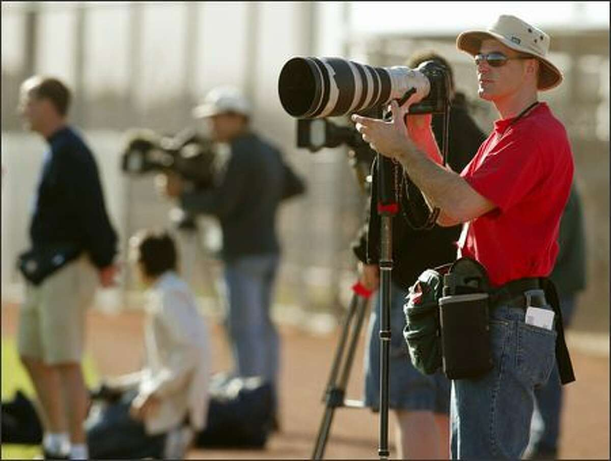 Seattle Post-Intelligencer photographer Mike Urban is shown on the job during Mariners spring training in Peoria, Ariz., in this picture captured by Seattle Times photographer Dean Rutz.
