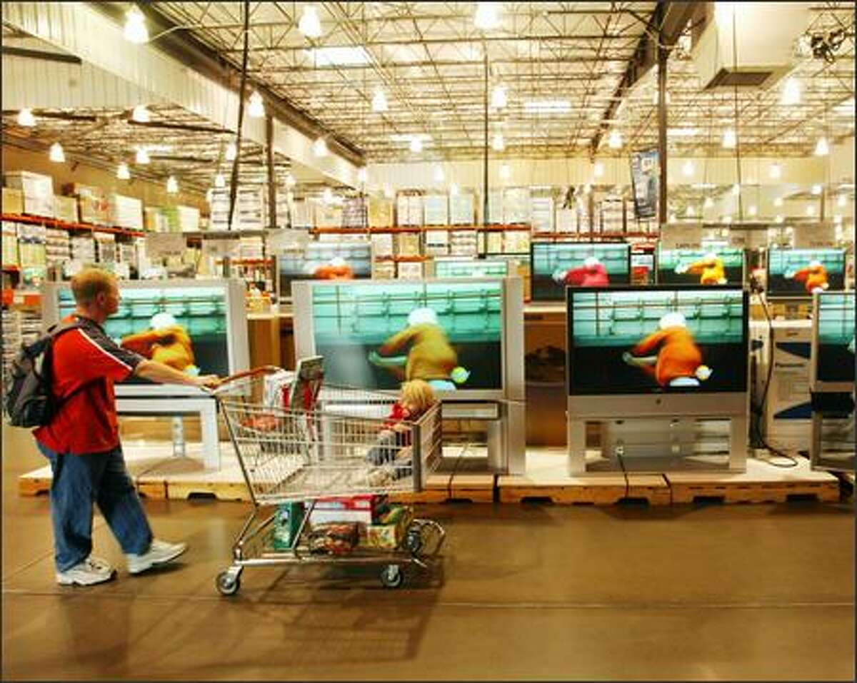 Paul Gibbons and his daughter Anna parade past big-screen TVs at the Issaquah Costco store. Architecture critic Lawrence Cheek believes the design of such big-box retail stores imparts feelings of anonymity and alienation.