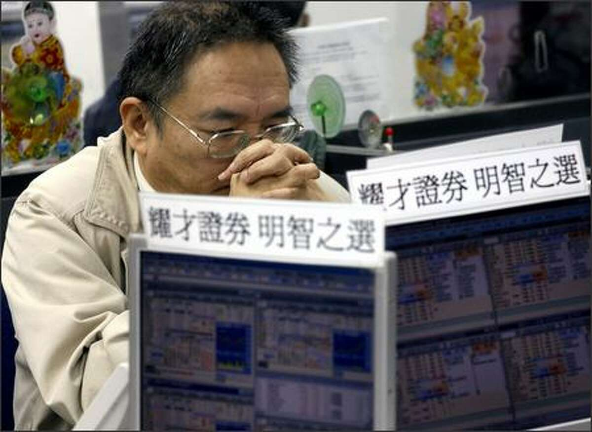 An investor watches a stock index at a securities firm in Hong Kong Wednesday. Hong Kong shares tumbled in early trading, tracking panic selling in global markets. The Hang Seng Index dropped 3.8 percent after opening.
