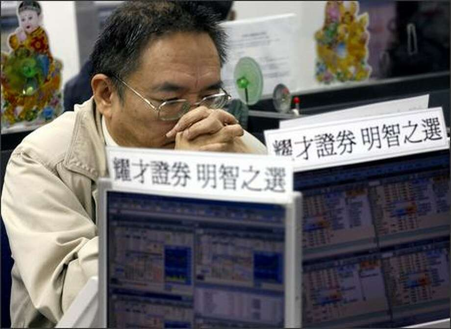 An investor watches a stock index at a securities firm in Hong Kong Wednesday. Hong Kong shares tumbled in early trading, tracking panic selling in global markets. The Hang Seng Index dropped 3.8 percent after opening. Photo: Associated Press / Associated Press