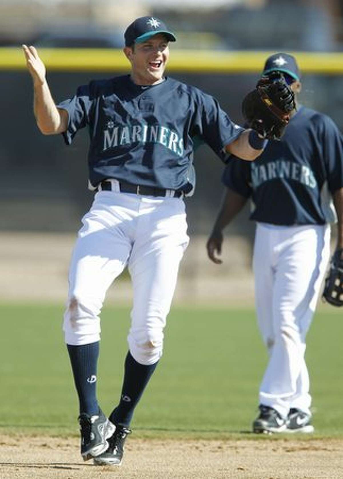 Seattle Mariners first baseman Mike Sweeney reacts after fielding the ball during a spring training baseball practice Thursday in Peoria, Ariz. (AP Photo/Charlie Neibergall)
