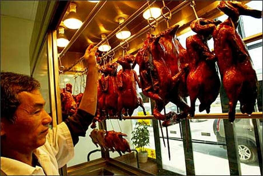 Whao Wu places ducks in the window at King's Barbecue House at 303 12th Ave. S. Below, a takeout duck is ready at King's. Photo: Phil H. Webber, Seattle Post-Intelligencer / Seattle Post-Intelligencer